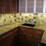 Sapele cabinets, glass tile backsplashes and granite countertops.